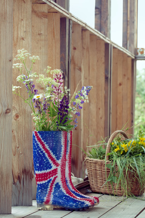 country house style: Bunch of wild flowers in Union Jack rubber boots-wellies on a country house wooden porch, natural outdoor shot Stock Photo