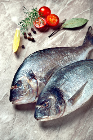 Two sea breams with tomatoes and herbs on kitchen table photo