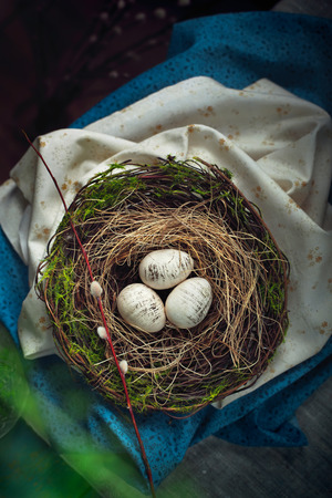 moss: Easter decoration - a nest with wooden eggs - on an old wooden table. Dark photo with space for text. Toned photo Stock Photo