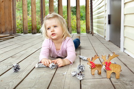 outdoor lighting: Little girl dreaming of Christmas and presents in summer while playing with Christmas decorations on a country house porch. Natural outdoor lighting setting.
