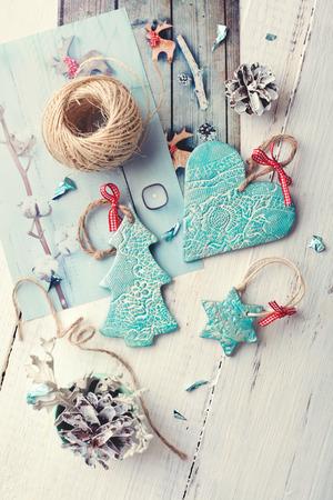 scandinavian christmas: Handmade ceramic Christmas decorations with Christmas theme printed photos, on wooden table. Toned photo.
