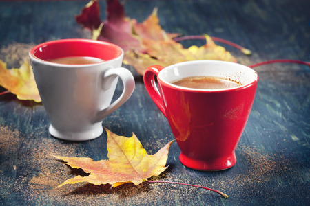cups of coffee: Two cups of coffee with autumn leaves, on wooden background, selective focus.