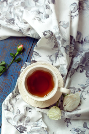 tea towel: Cup of tea set with a beautiful tea towel and roses on a wooden table, toned photo