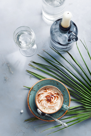 Cup of cappuccino set with modern and exotic accessories - palm leaf, candles and candleholders. Chilling out at bar by sea coffee consumingholiday and travel concepts.