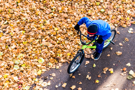 Overhead photo of a boy rides a bicycle in autumn park.
