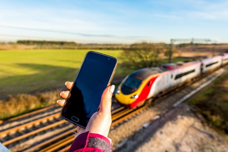 Day view of woman hand holding smartphone over UK Railroad. Stock Photo