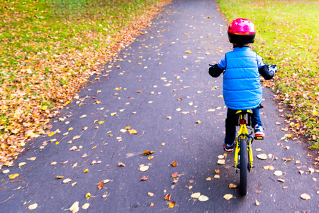 Overhead view of a boy riding bike with safety helmet outdoors at autumn park.