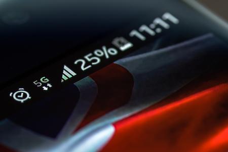 Smartphone op houten achtergrond met 5G netwerkteken 25 procent lading en Britse vlag op het scherm. Stockfoto