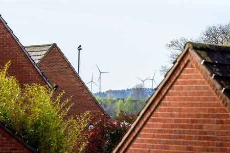 climatic: View of roofs near town and wind turbines