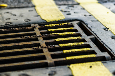 Closeup view of yellow road marking on sewer grate