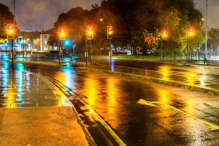 Night rain view yellow traffic lights at UK roundabout
