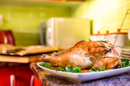 Closeup view of roasted chicken on white plate on kitchen table. Stock Photo