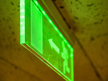 Indoor view green emergency fire exit sign on ceiling