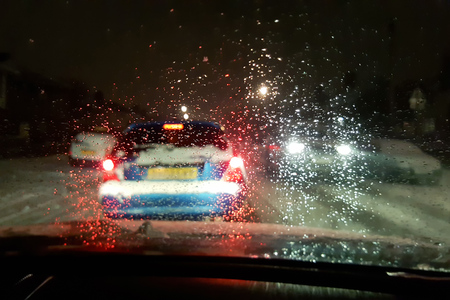 In car view of snow fall storm in the UK causes traffic congestion at night Stock Photo