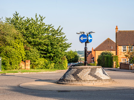 Day view of typical english brick roundabout with directional signs