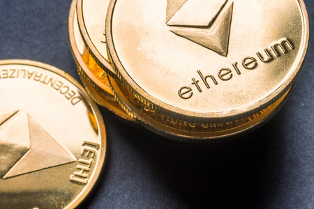Overhead Golden virtual money Ethereum crypto currency coins stacked on a dark background
