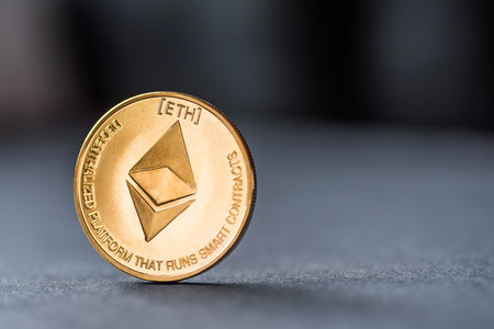 Golden virtual money Ethereum crypto currency coin on a dark background