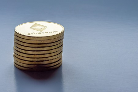 Golden virtual money Ethereum crypto currency coins stacked on a dark background Stock Photo