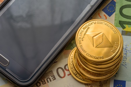 Ethereum coins stacked on Euro notes next to smartphone, future concept financial currency, crypto currency sign Stock Photo