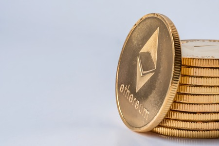 Golden virtual money Ethereum crypto currency coins stacked on bright background Stock Photo
