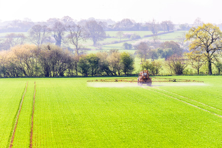 Sunny day view of tractors spraying British field