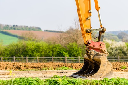 A large yellow construction excavator bucket over British countryside ready for quarrying Stock Photo