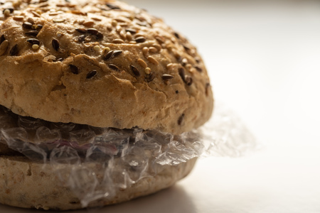 Fresh tasty burger with plastic waste and paper cardboard inside on white background. Recycled waste in our food concept