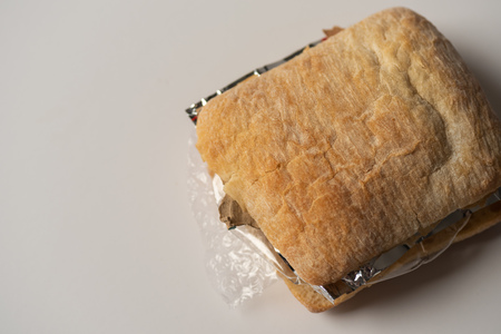 Fresh tasty panini sandwich with plastic waste and paper cardboard inside on white background. Recycled waste in our food concept