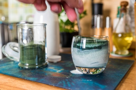 Closeup view fresh kefir probiotik drink in clear glass and spoon with green spirulina powder ready to mix on kitchen table