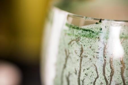 Closeup view emptied glass of fresh kefir probiotik drink mixed with green spirulina powder on kitchen table Stockfoto