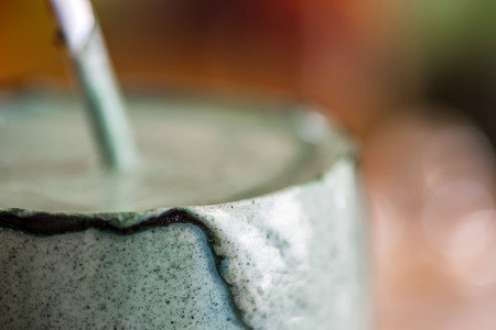 Closeup view fresh kefir probiotik drink in clear glass mixed with green spirulina powder on kitchen table