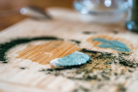 Closeup view fresh kefir probiotik drink and green spirulina powder leftovers on wooden board after mixing on kitchen table Stockfoto