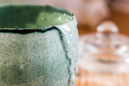 Closeup view emptied glass of fresh kefir probiotik drink mixed with green spirulina powder on wooden board on kitchen table