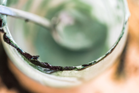 Overhead closeup view emptied glass with spoon of fresh kefir probiotik drink mixed with green spirulina powder on kitchen table Stockfoto