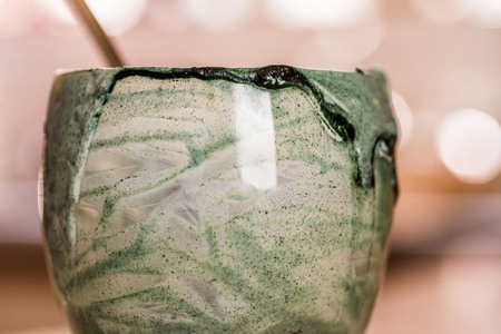 Closeup view emptied glass of fresh kefir probiotik drink mixed with green spirulina powder with spoon inside on kitchen table