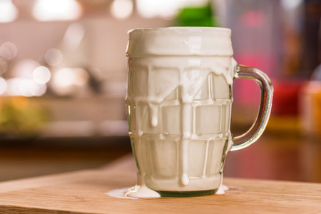 Closeup view fresh kefir probiotik drink in overfilled clear glass cup on kitchen table Stockfoto