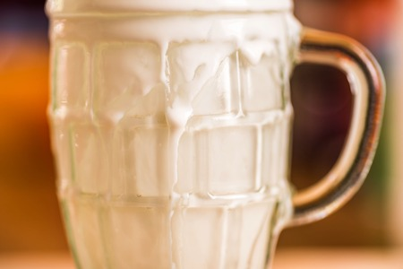 Closeup view fresh kefir probiotik drink emerged from overfilled empty glass on kitchen table