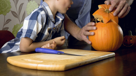 Young boy with his father carving a pumpkin for Halloween on a table. Stock Photo