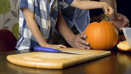 Young boy with his father carving a pumpkin for Halloween on a table. Stockfoto