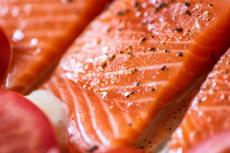 Closeup view fresh raw salmon fillets with herbs and spices on baking tray ready to be cooked in oven. Stockfoto