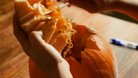 Young boy carving and painting a pumpkin for Halloween on a table.