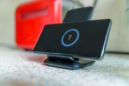 smartphone wireless charging on charging stand with 21 percent icon on screen on kitchen tabletop next to toaster.