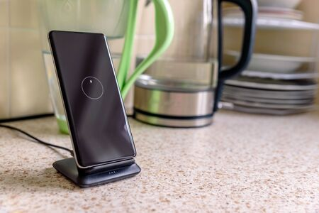 smartphone wireless charging on charging stand on kitchen tabletop