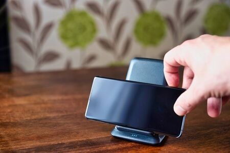 smartphone wireless charging on charging stand on wooden table. male hand placing phone to charging