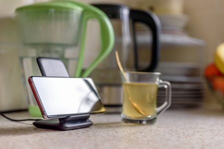 smartphone wireless charging on charging stand next to tea glass cup on kitchen tabletop Stock fotó