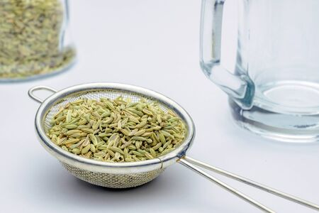 fennel seeds loose inside sieve ready to be brewed for healthy drink on white background