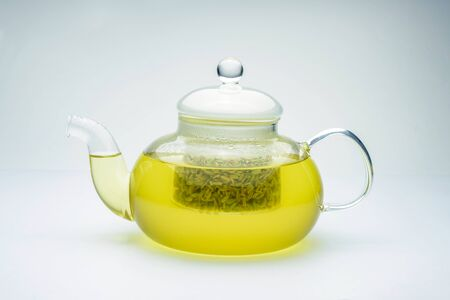 fennel seeds loose inside glass teapot brewed for healthy drink on white background.