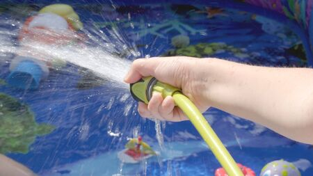 Filling Inflatable pool with water from hose in garden.