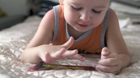 child boy watch play smartphone on bed at home. distance learning education