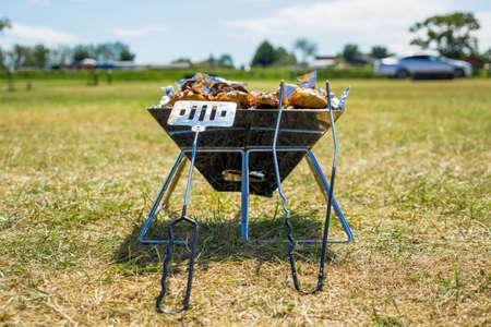 烤在一个便携式烤肉的热的煤炭烤在绿色草坪。野餐或夏季野营旅行